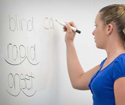 High school student marking up words on the board